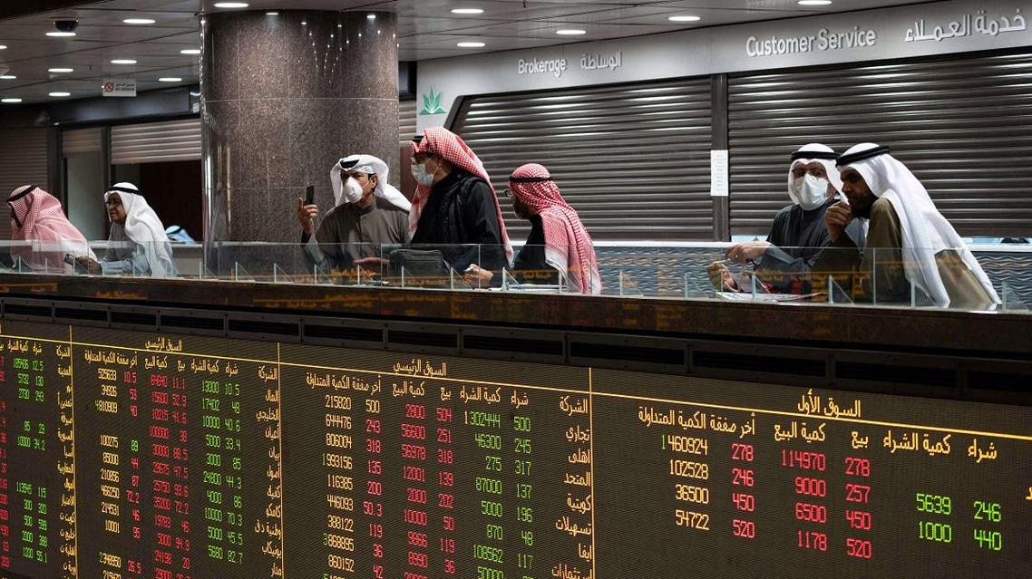 Kuwaiti traders wear protective face masks, following the outbreak of the new coronavirus, as they stand on the upper floor since the lower main hall is closed to traders at the Kuwait Boursa stock market trading in Kuwait city, Kuwait, March 1, 2020. (Reuters)