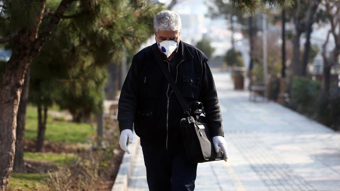 An Iranian man wears a protective mask to prevent contracting coronavirus, as he walks on a street in Tehran, Iran. (Reuters)