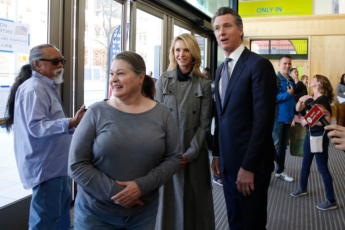 California Governor Gavin Newsom (right), waits in line to vote with his wife, Jennifer Siebel Newsom, second from right, on Super Tuesday in Sacramento, California, on March 3, 2020. (AP)