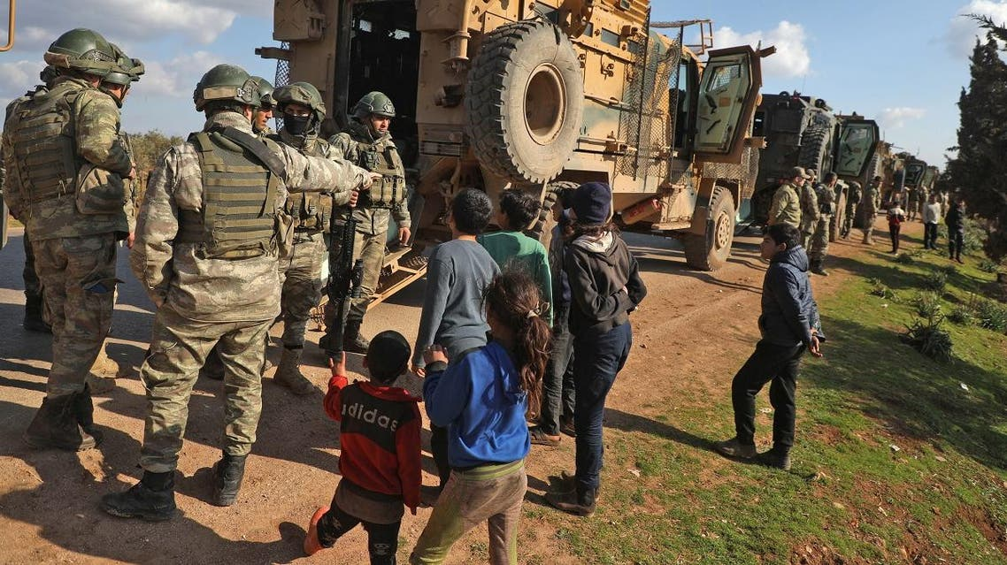 Displaced Syrian children speak with Turkish soldiers as their convoy is parked near the town of Batabu on the highway linking Idlib to the Syrian Bab al-Hawa border crossing with Turkey, on March 2, 2020. (AFP)