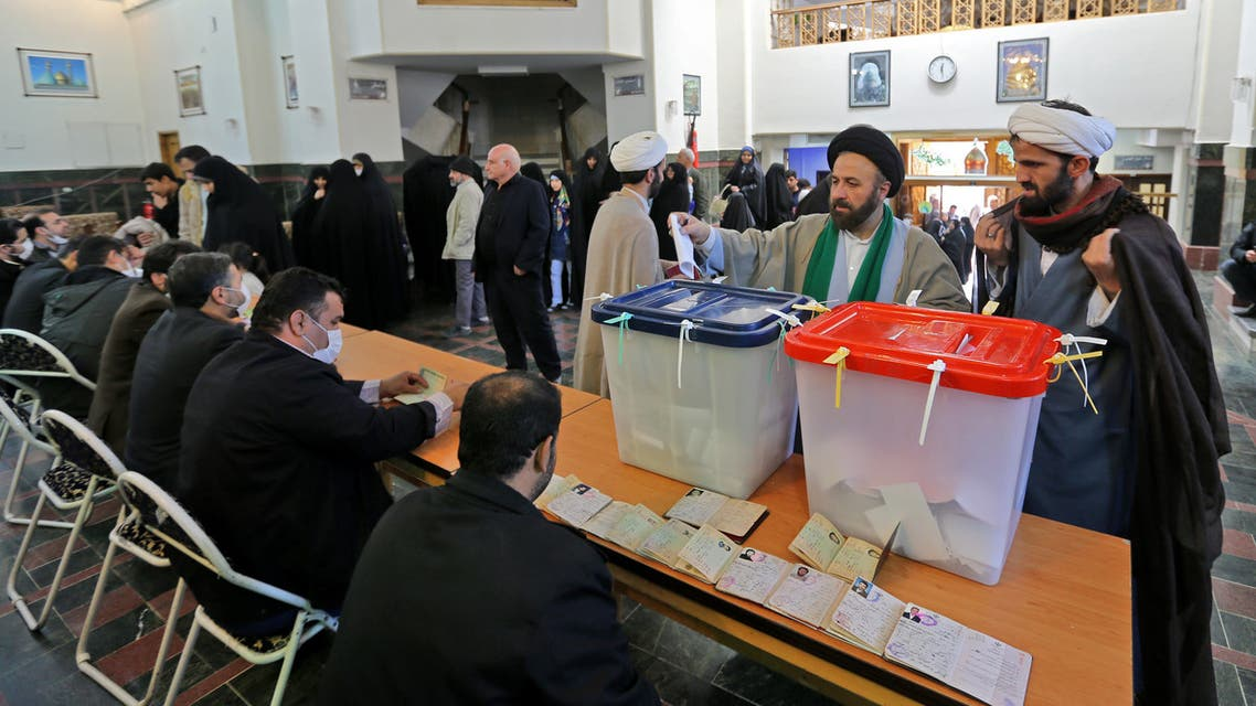 Iranian election officials wear masks as they wait for voters during parliamentary elections at the Shah Abdul Azim shrine on the southern outskirts of Tehran on February 21, 2020. Iran's health ministry today reported two more deaths among 13 new cases of coronavirus in the Islamic republic, bringing the total number of deaths to four and infections to 18.
