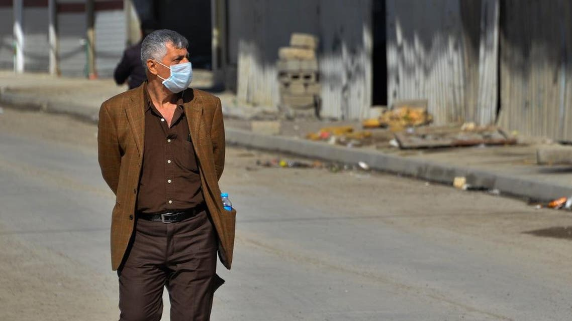 An Iraqi man wearing a protective mask walks in a deserted street in the northern Iraqi city of Mosul. (File photo: AFP)