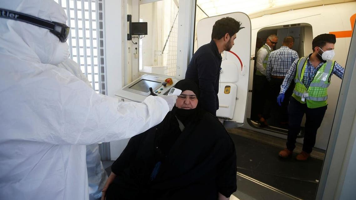 A member of medical staff in protective gear checks passengers' temperature, following an outbreak of the coronavirus, upon their arrival at Basra airport, in Basra, Iraq, March 3, 2020. (Reuters)