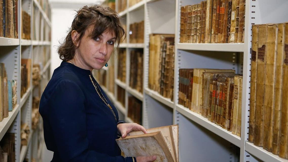 Librarian Vannina Schirinsky-Schikhmatoff poses for a photo session as she holds an old book in the reserve of the Fesch Heritage library, in Ajaccio on the French Mediterranean island of Corsica, on May 24, 2019. (AFP)