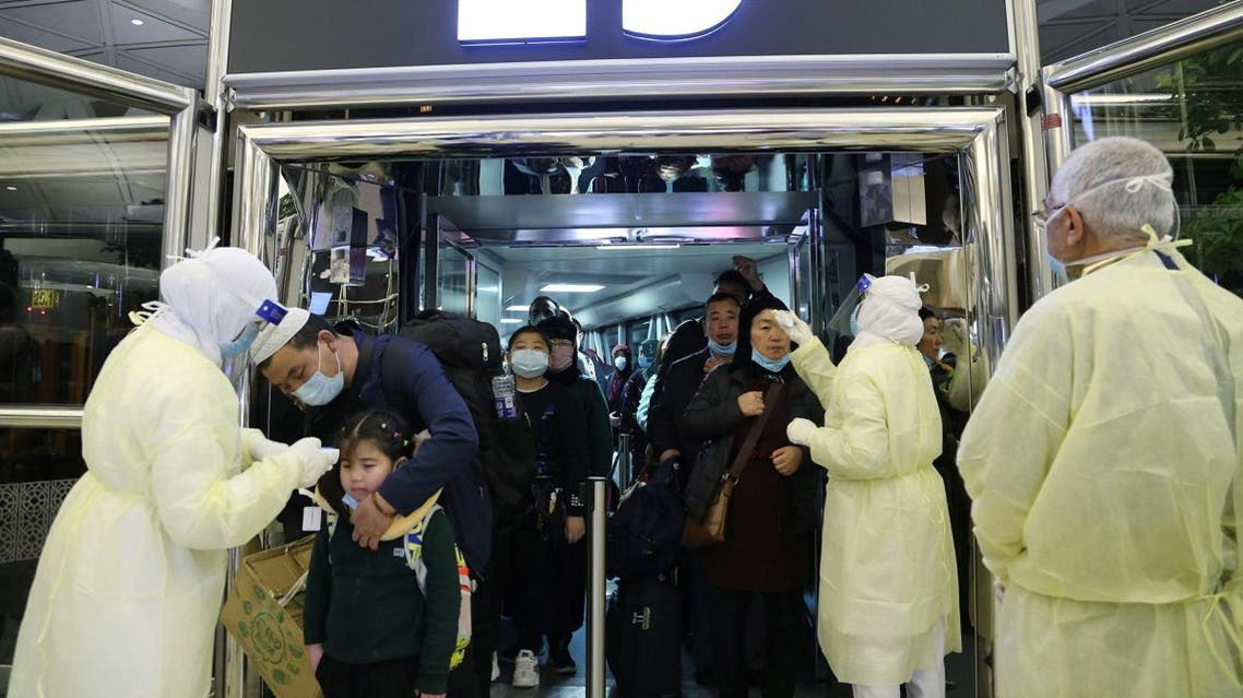 Passengers coming from China wearing masks to prevent a new coronavirus are checked by Saudi Health Ministry employees upon their arrival at King Khalid International Airport, in Riyadh. (Reuters)