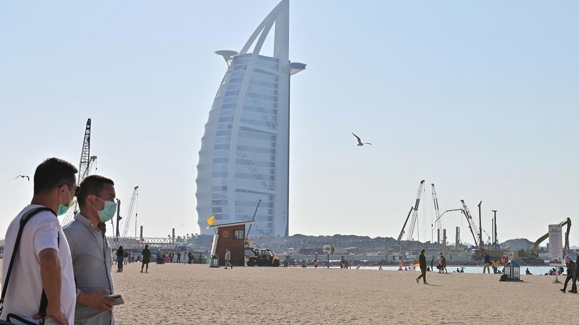 Tourists wearing surgical masks are pictured on a beach next to Burj Al Arab in Dubai on January 29 2020. (AFP)