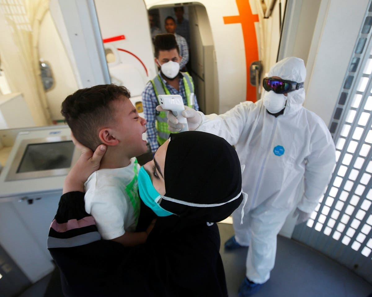 A member of medical staff in protective gear checks a child temperature, following an outbreak of the coronavirus, upon his arrival with his family at Basra airport, in Basra, Iraq, March 3, 2020. (Reuters)
