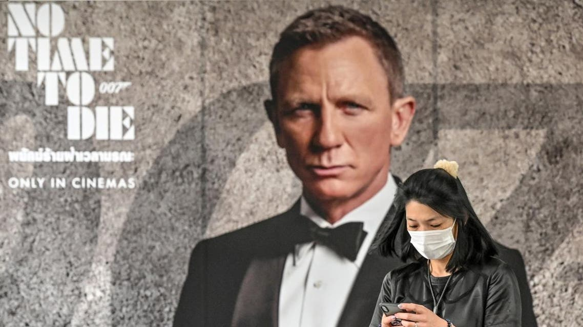 """A woman wearing a facemask amid fears of the spread of the novel coronavirus walks past a poster for the new James Bond movie """"No Time to Die"""" in Bangkok. (AFP)"""