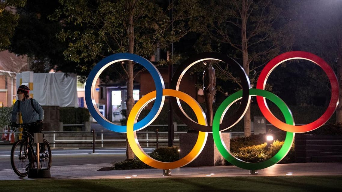 A woman wearing a protective face mask, following the outbreak of the coronavirus, rides her bicycle past The Olympic rings in front of the Japan Olympics Museum in Tokyo, Japan, March 3, 2020. (Reuters)