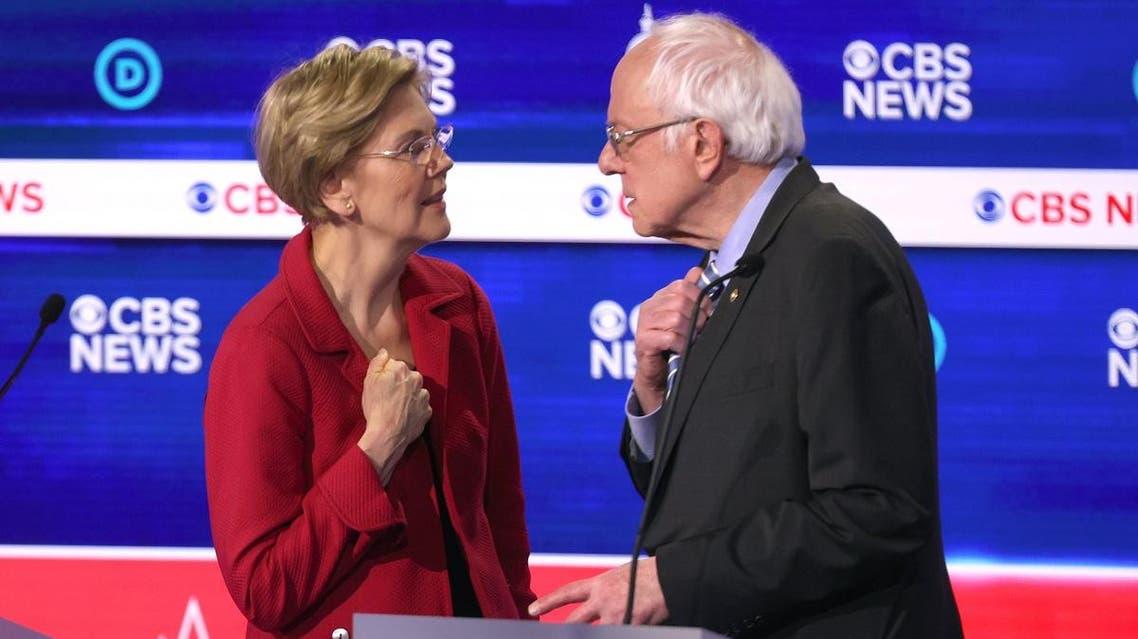 Democratic presidential candidates Sen. Elizabeth Warren (D-MA) (L) and Sen. Bernie Sanders (I-VT) interact during a break at the Democratic presidential primary debate at the Charleston Gaillard Center on February 25, 2020 in Charleston, South Carolina. (AFP)