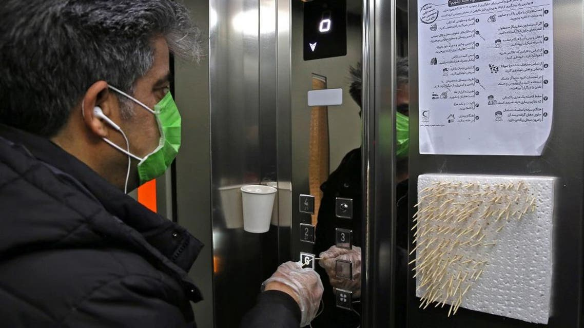 An Iranian man uses small sticks to push the elevator button at an office building in Tehran AFP