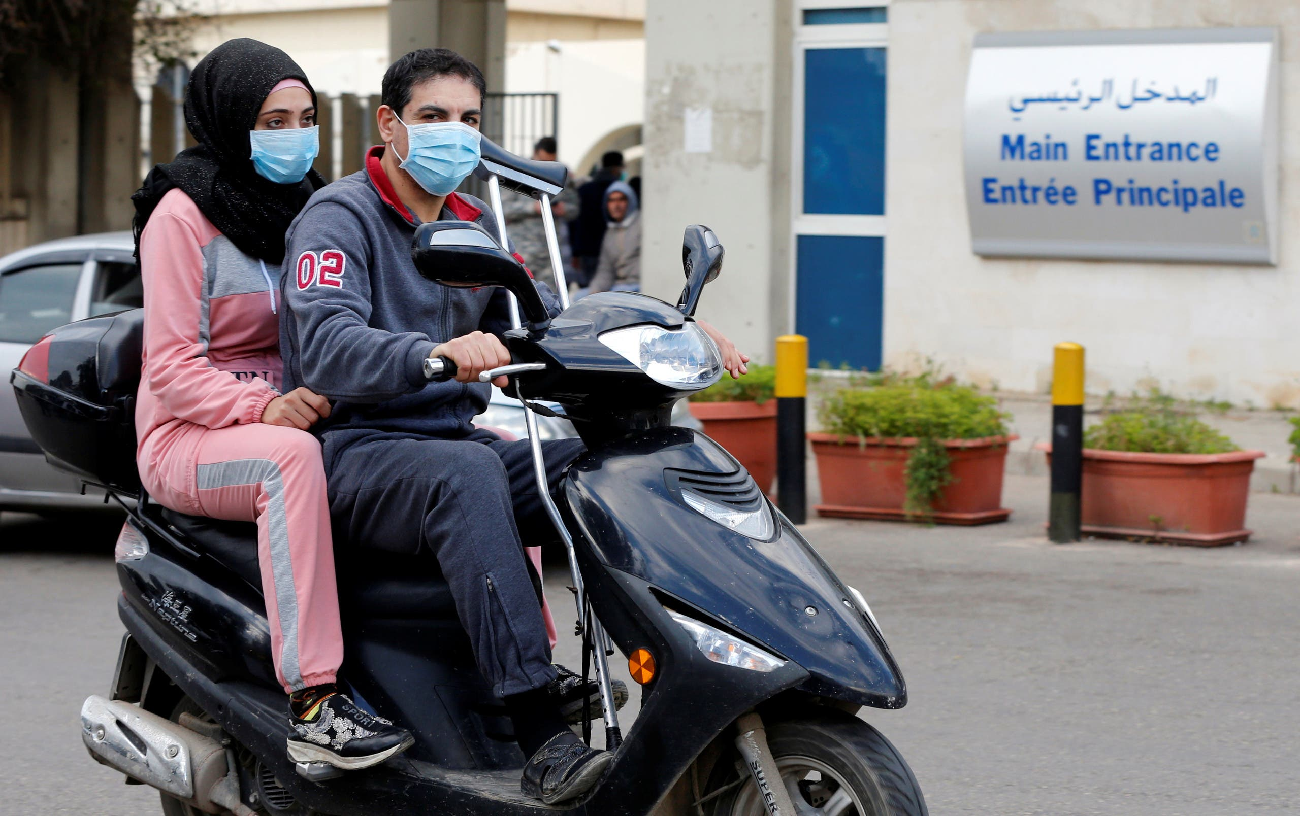 People wearing face masks ride on a motorbike outside Rafik Hariri hospital, where Lebanon's first coronavirus case is being quarantined, in Beirut, Lebanon. (Reuters)