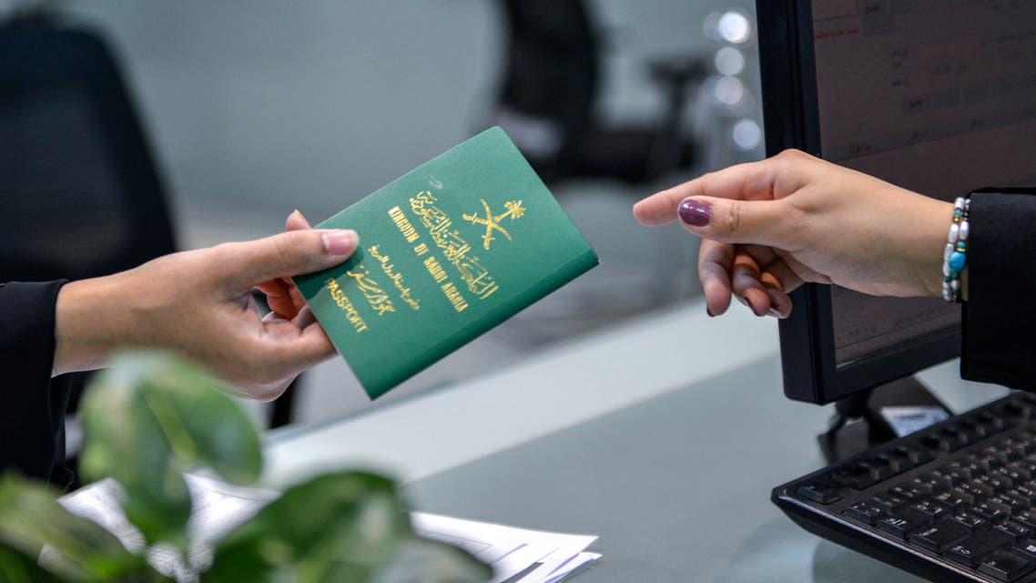 A Saudi woman receives her newly-issued passport at the Immigration and Passports Centre in the capital Riyadh on August 29, 2019. Saudi Arabia has eased travel restrictions on women, allowing those aged over 21 to obtain passports without seeking the approval of their guardians -— fathers, husbands or other male relatives, but observers say loopholes still allow male relatives to curtail their movements and, in the worst cases, leave them marooned in prison-like shelters.