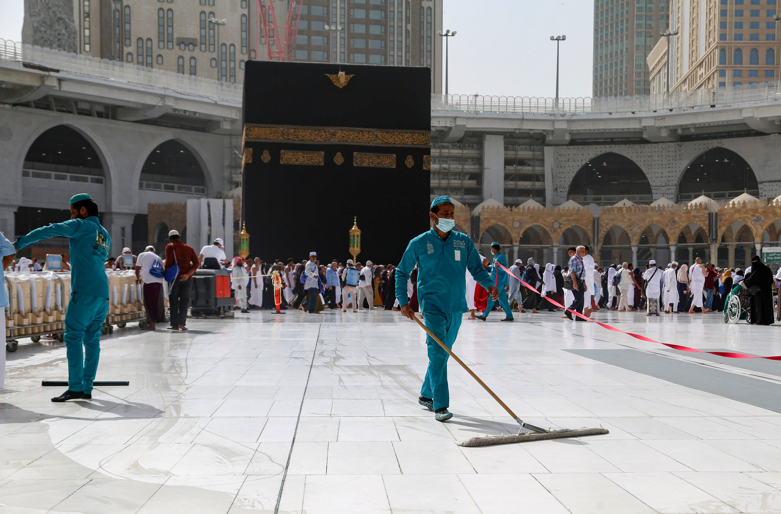 Cleaners wear protective face masks as they swipe the floor at the Kaaba in the Grand mosque. (File photo: Reuters)