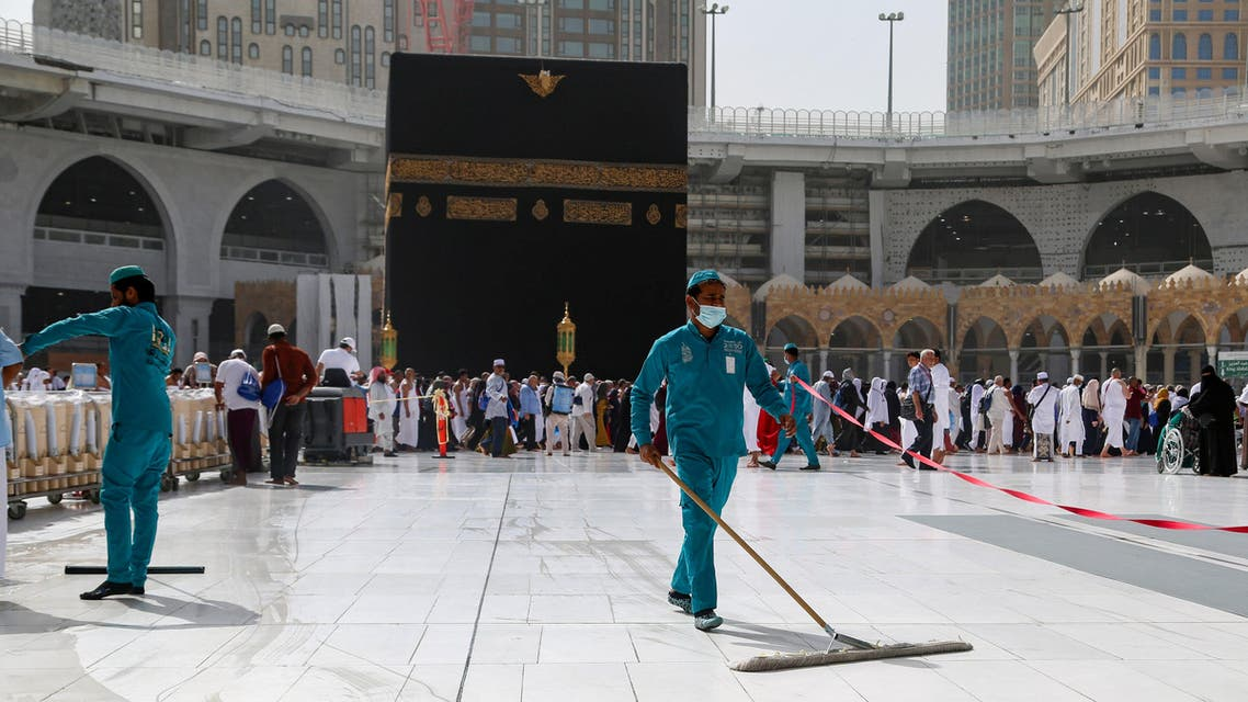 Cleaners wear protective face masks, following the outbreak of the coronavirus, as they swipe the floor at the Kaaba in the Grand mosque in the holy city of Mecca, Saudi Arabia, March 3, 2020. (Reuters)