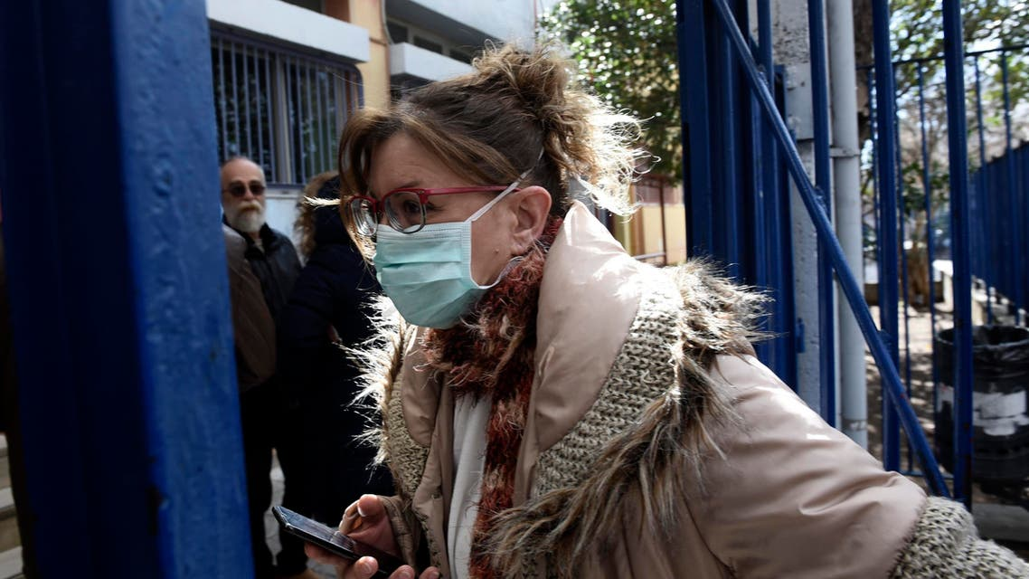 A woman wearing a face mask enters a primary school where a child was diagnosed with coronavirus in the northern city of Thessaloniki, Greece on Feb. 27, 2020. (AP)