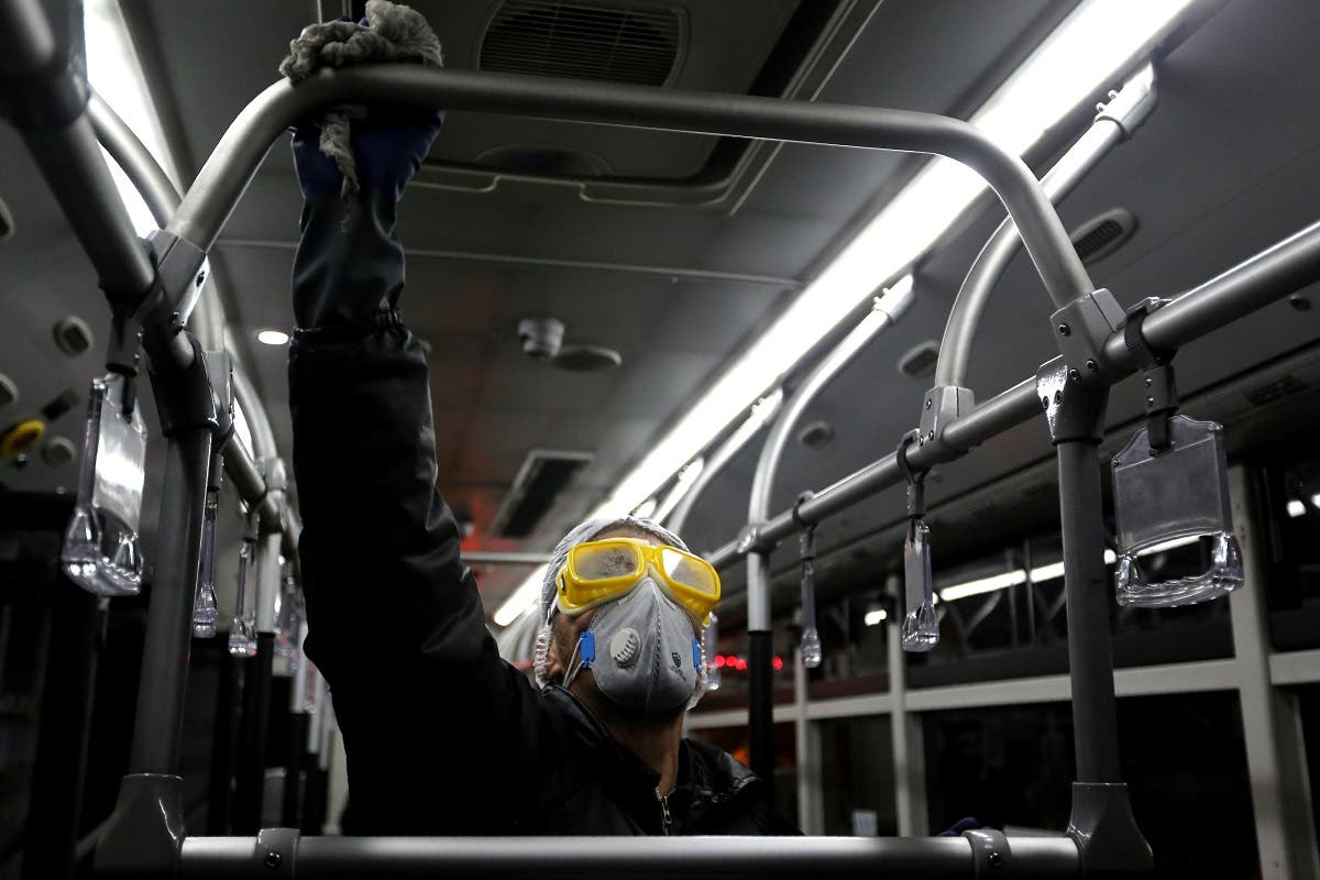 A Tehran Municipality worker cleans a bus to avoid the spread of the COVID-19 illness on February 26, 2020. (AFP)