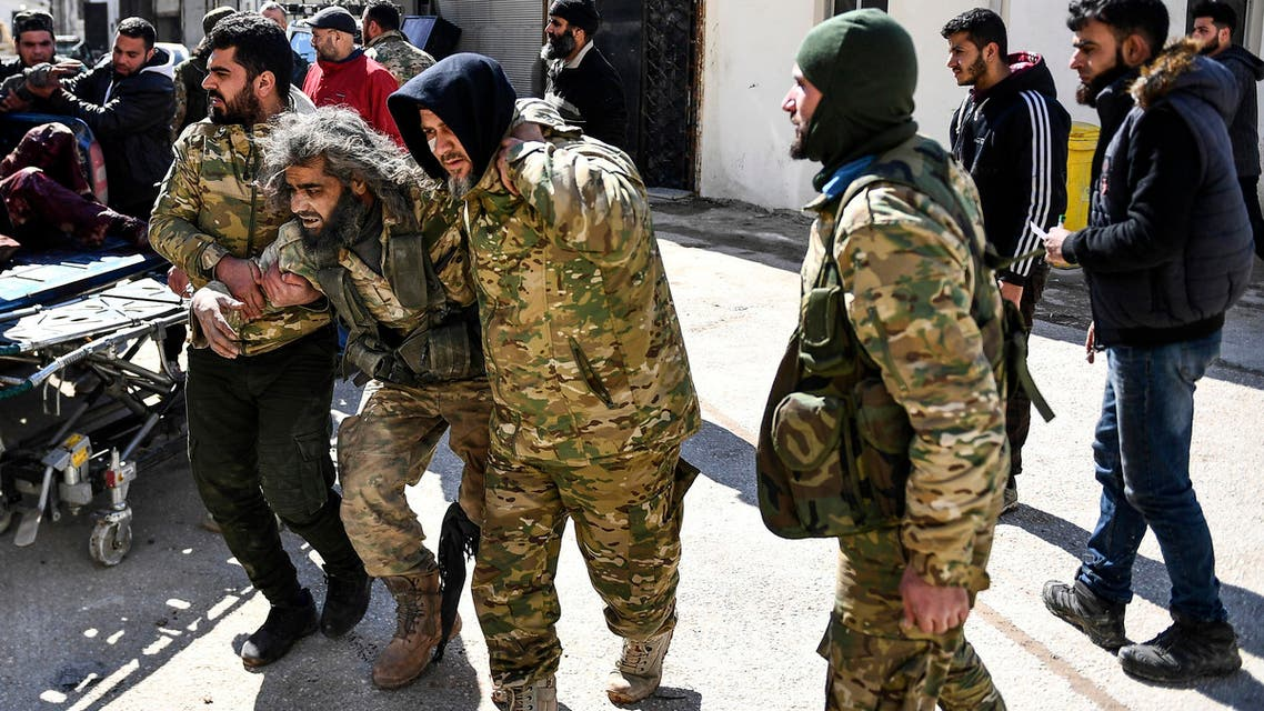 Turkey-backed opposition fighters help a fellow fighter wounded in fighting with Syrian government forces and their allies in Sarmin, south of Idlib on March 1, 2020. (AP)