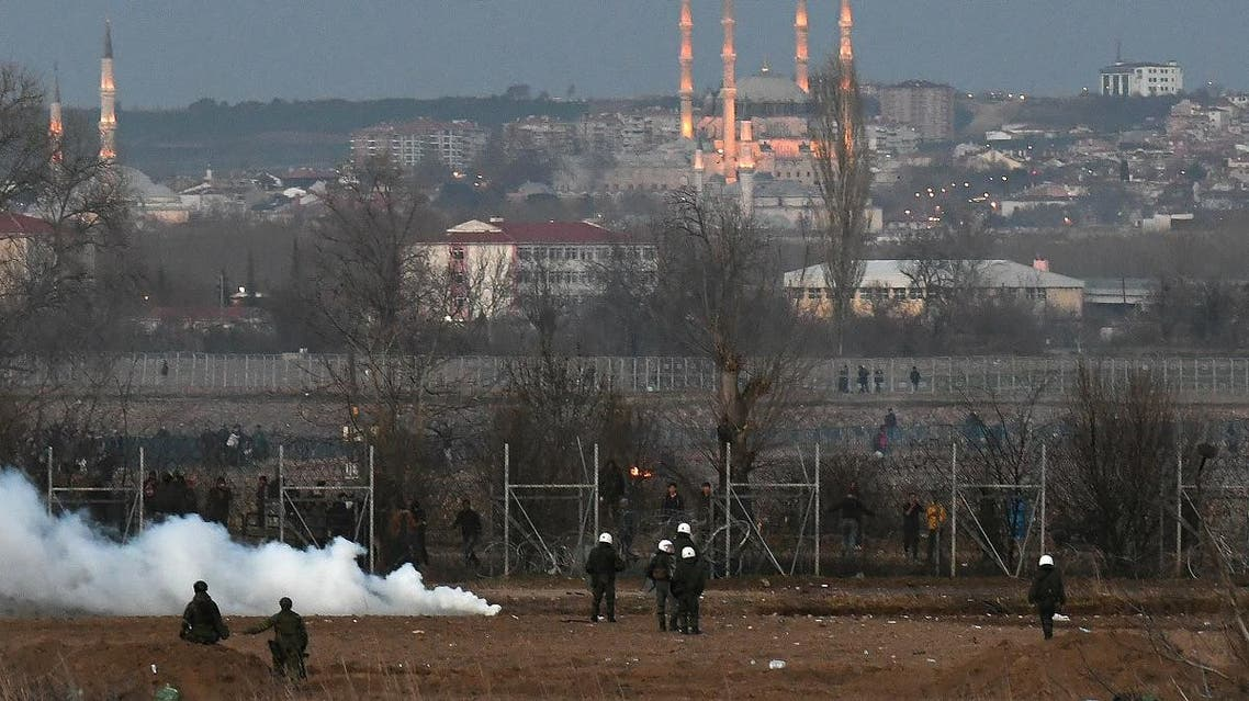 Greek riot police officers stand guard next to tear gas, as migrants are seen on the other side of the border fence, near Greece's Kastanies border crossing with Turkey's Pazarkule, Greece March 7, 2020. (Reuters)