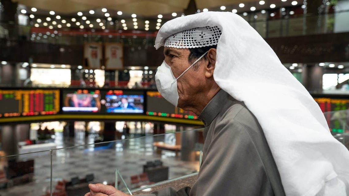 A Kuwaiti trader wears a protective face mask, following the outbreak of the new coronavirus, as he stands on the upper floor since the lower main hall is closed to traders at the Kuwait Boursa. (Reuters)