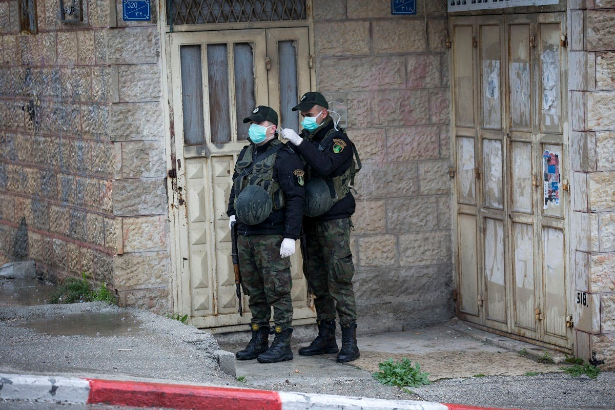 Members of Palestinian security forces wear masks as they stand guard outside a hotel which staff tested positive for coronavirus in Bethlehem, West Bank, Palestine (AP)