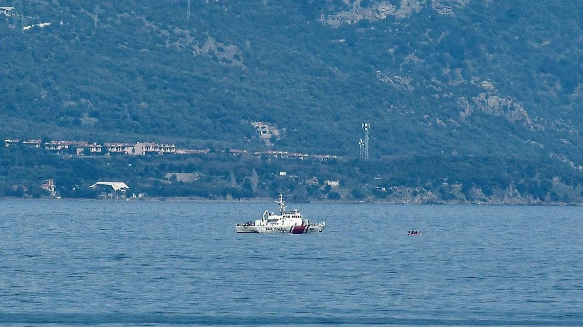 Turkish coastguard boat proceeds to check a inflatable boat at the sea between Lesbos island and the Turkish coast as part of operations to prevent boats of refugees of reaching the Greek coast on March 6, 2020. (AFP)
