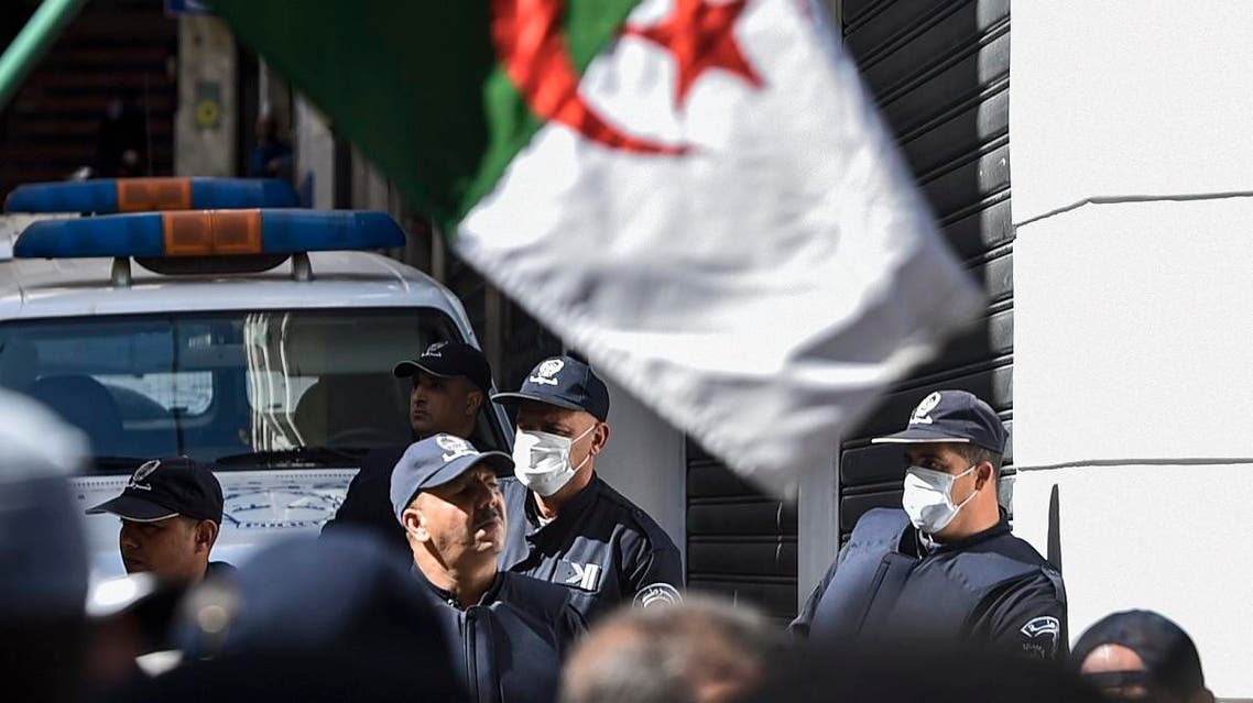 Algerian anti-riot police members wearing protective health masks stand as protesters march past them during a weekly anti-government demonstration in the capital Algiers on March 6, 2020. (AFP)