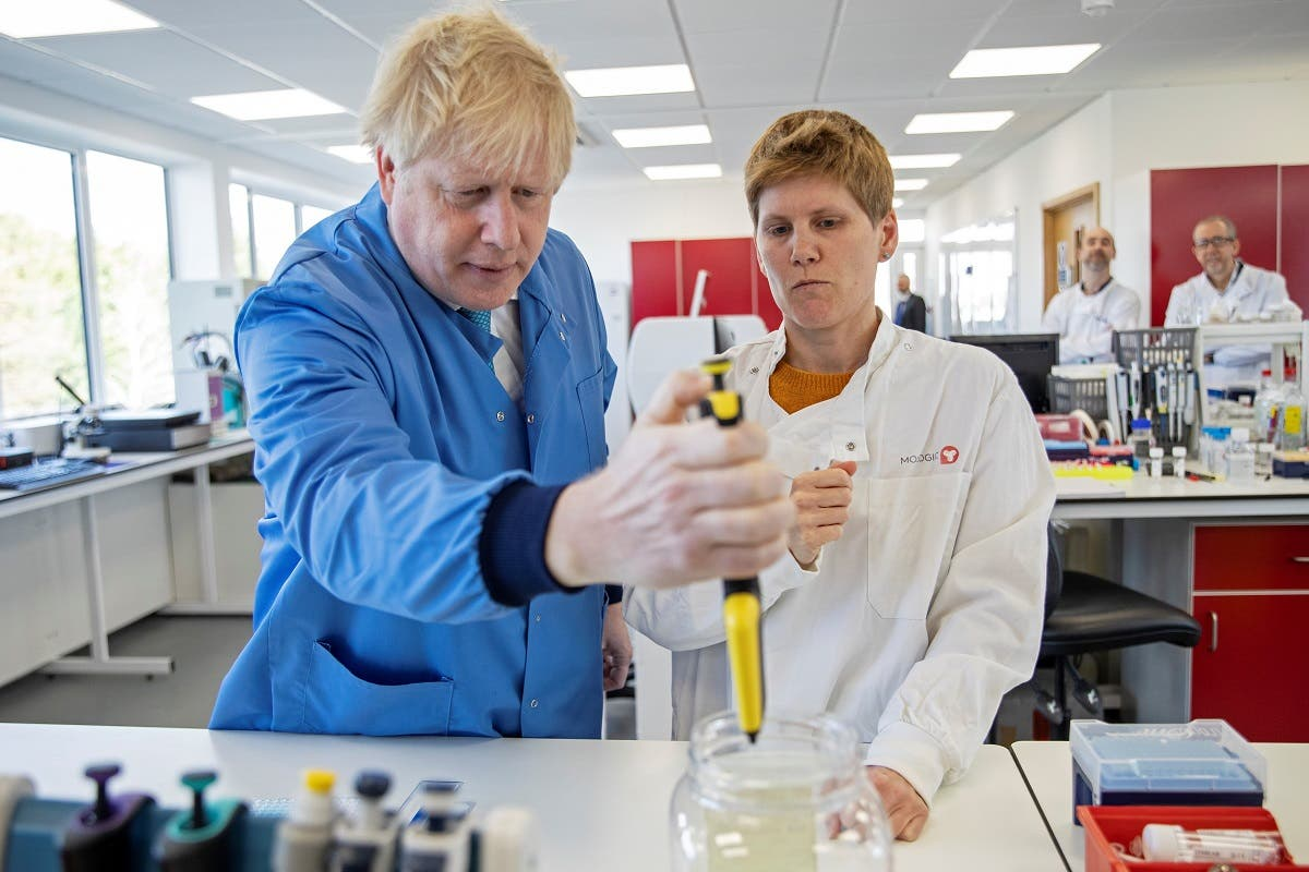 Britain's Prime Minister Boris Johnson (1st-L) visits to the Mologic Laboratory in the Bedford technology Park, north of London on March 6, 2020. (AFP)