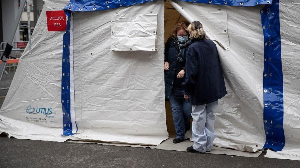A nurse escorts a patient with covid-19 symptoms to a tent set up in a courtyard of the Henri Mondor Hospital in Creteil, near Paris. (Reuters)