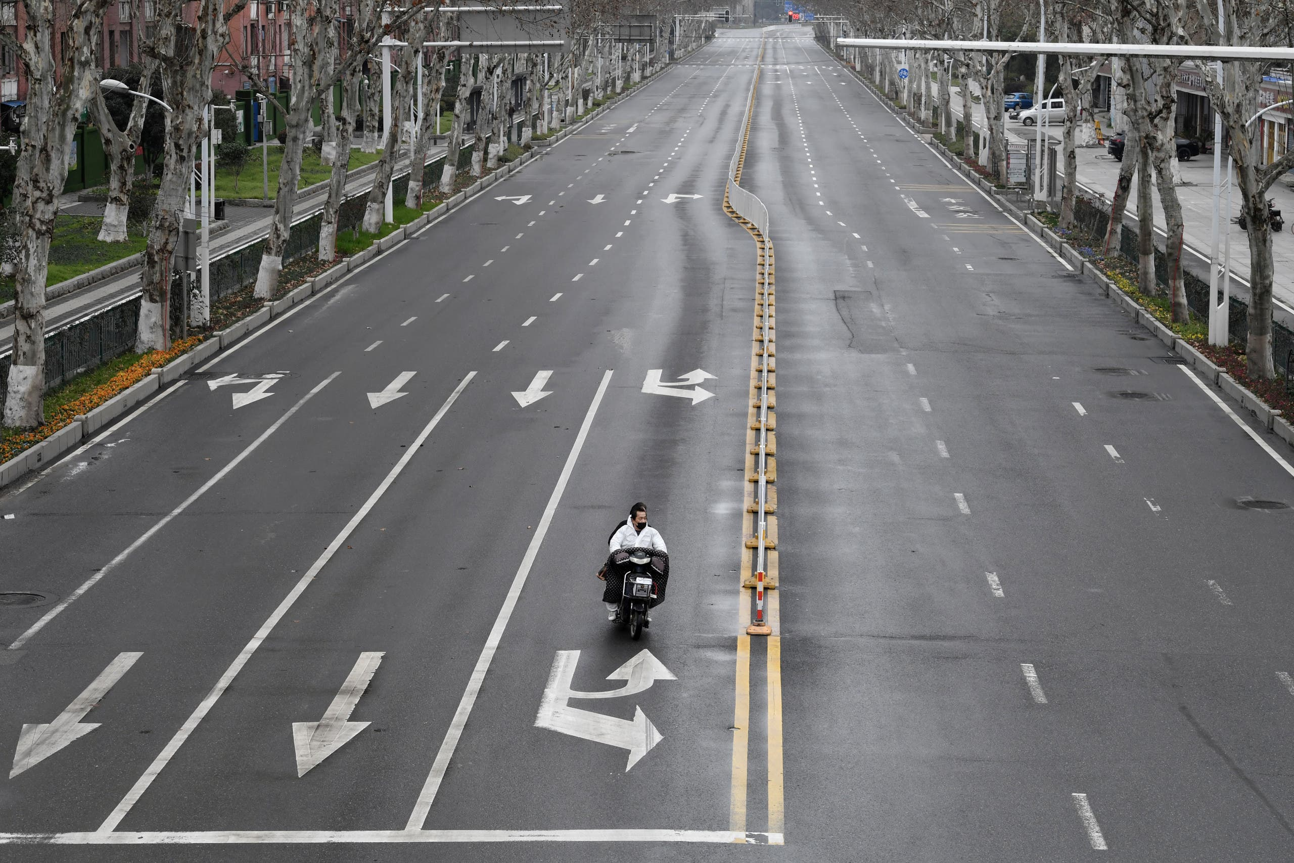 People ride an electric bike on a road in Wuhan, the epicentre of the novel coronavirus outbreak, Hubei province, China. (File photo: Reuters)