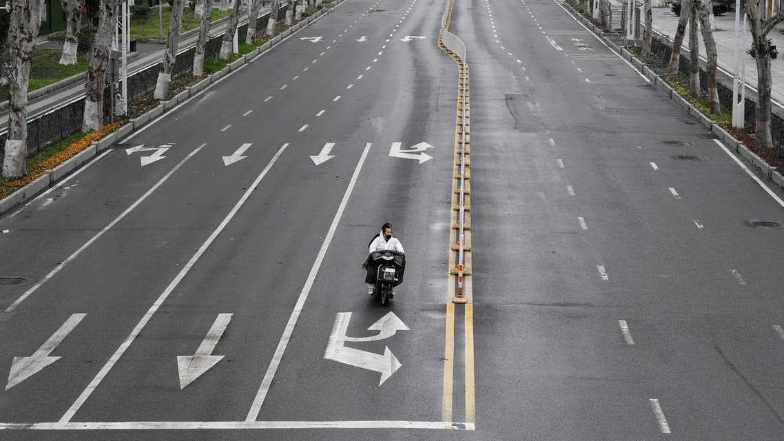 People ride an electric bike on a road in Wuhan, the epicentre of the novel coronavirus outbreak, Hubei province, China March 3, 2020. REUTERS/Stringer CHINA OUT.
