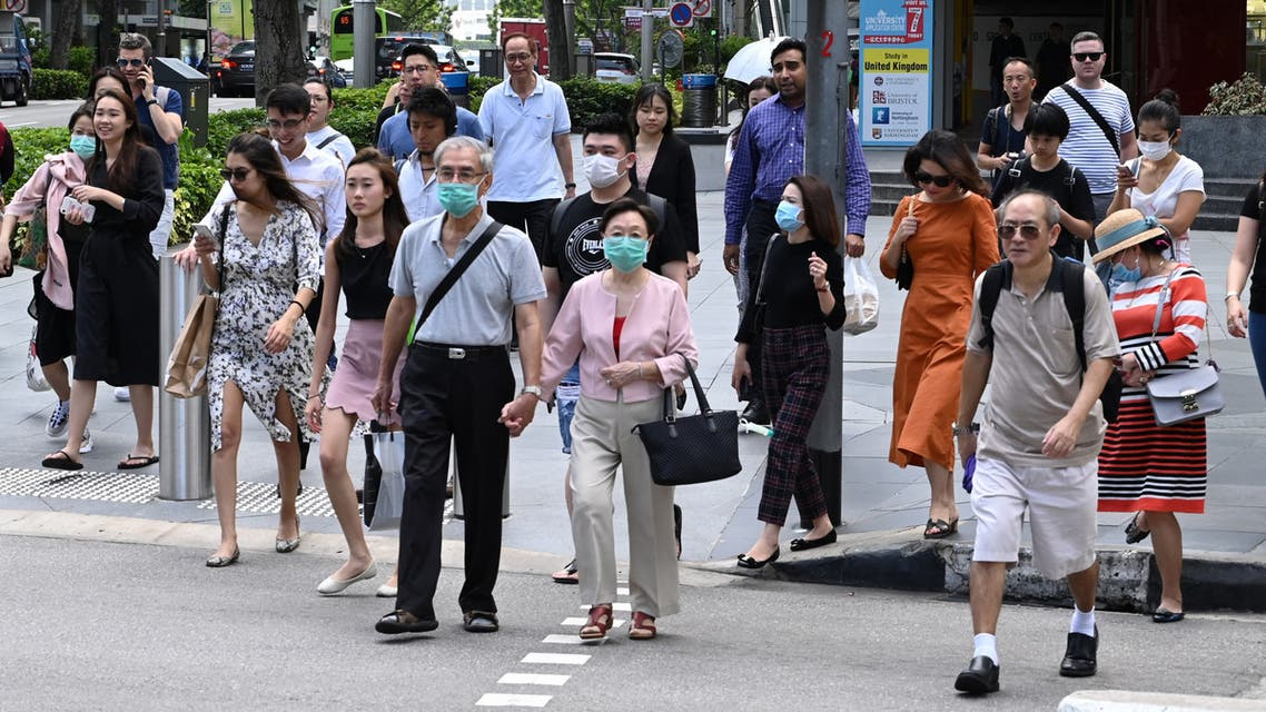 People, some wearing a protective facemask amid fears about the spread of the COVID-19 novel coronavirus, crosses the road in Singapore on February 26, 2020. (Photo by Roslan RAHMAN / AFP)