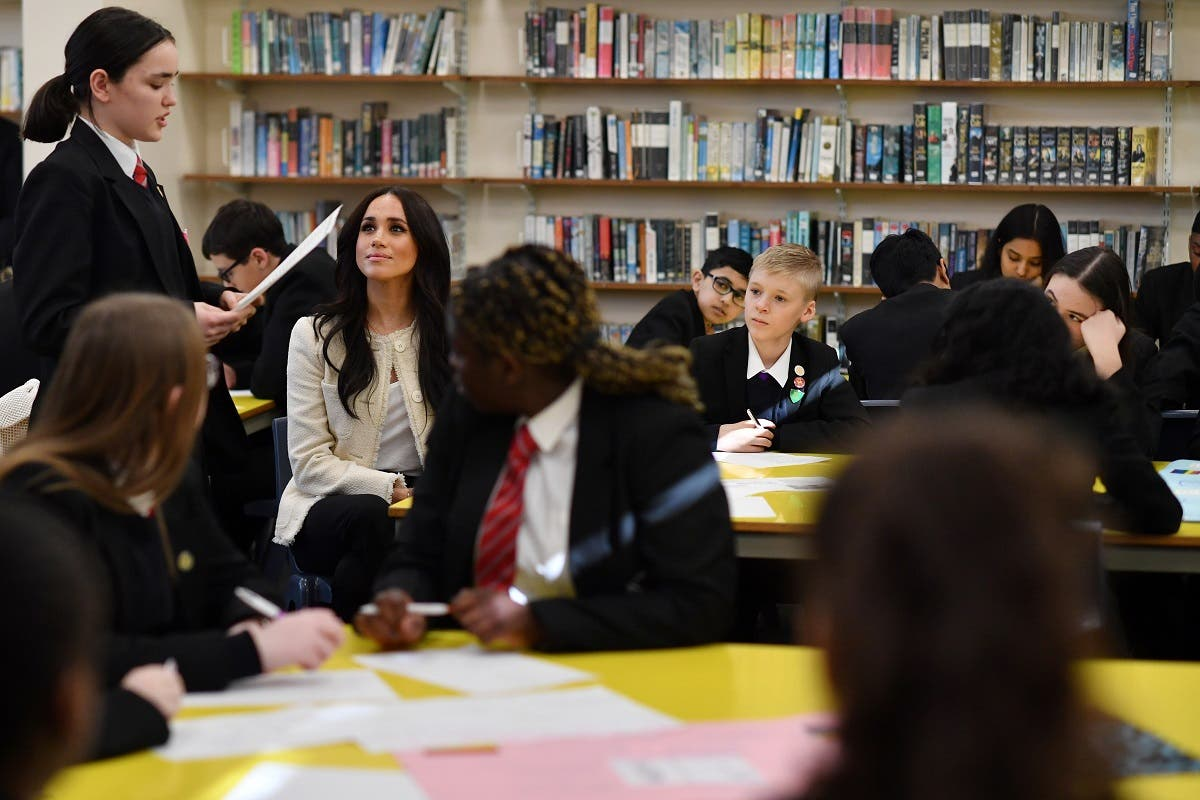Britain's Meghan, Duchess of Sussex, listens to a student reciting a poem during a visit to Robert Clack School in Essex, on March 6, 2020, in support of International Women's Day. (AFP)
