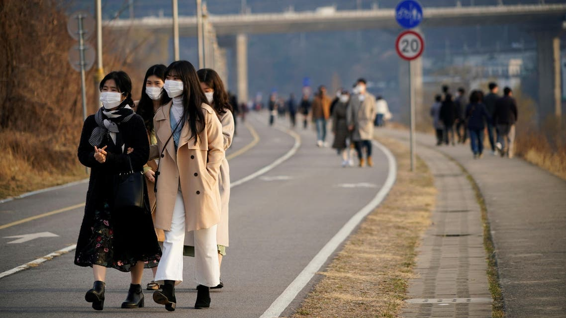 Women wearing masks to prevent contracting the coronavirus take a walk at a Han River park in Namyangju, South Korea, March 7, 2020. (Reuters)