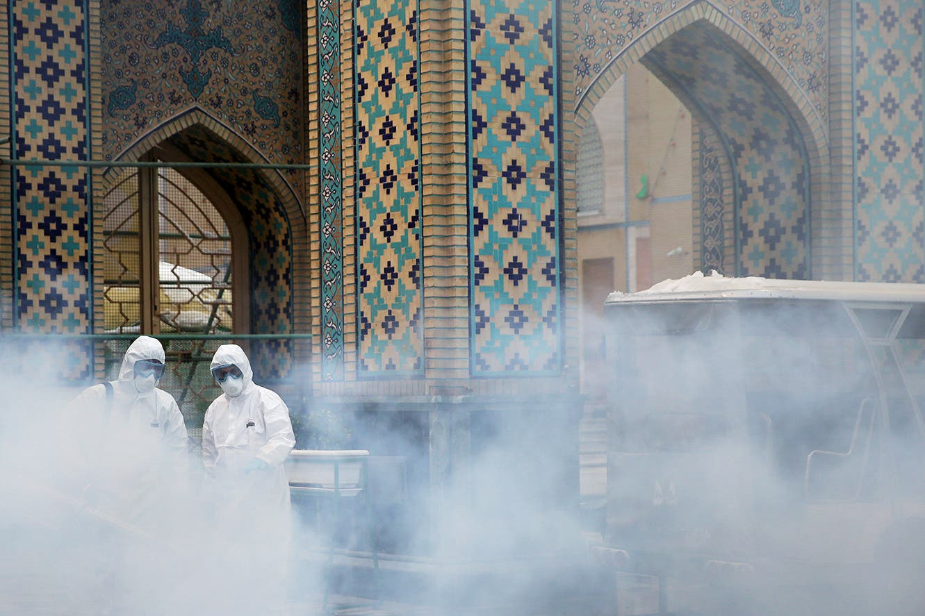 Members of the medical team spray disinfectant to sanitize outdoor place of Imam Reza's holy shrine, following the coronavirus outbreak, in Mashhad, Iran February 27, 2020. (Reuters)