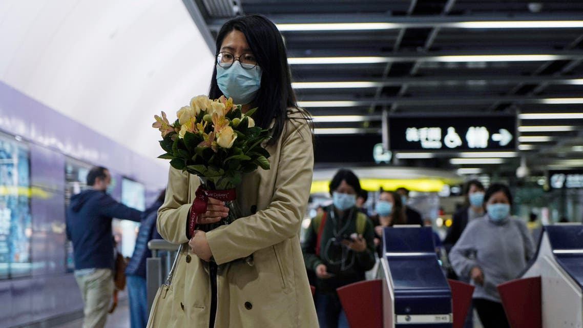 A woman wearing a mask holds a bunch of flower as a precaution against coronavirus at a subway station in Hong Kong on March 6, 2020. (AP)