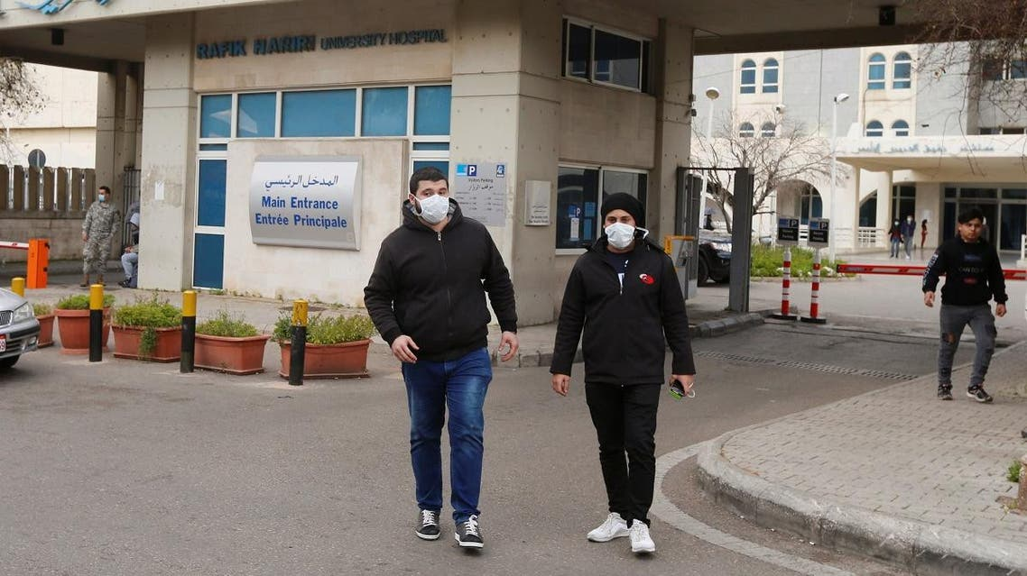 People wearing face masks walk outside Rafik Hariri hospital, where Lebanon's first coronavirus case is being quarantined, in Beirut, Lebanon February 21, 2020. (Reuters)
