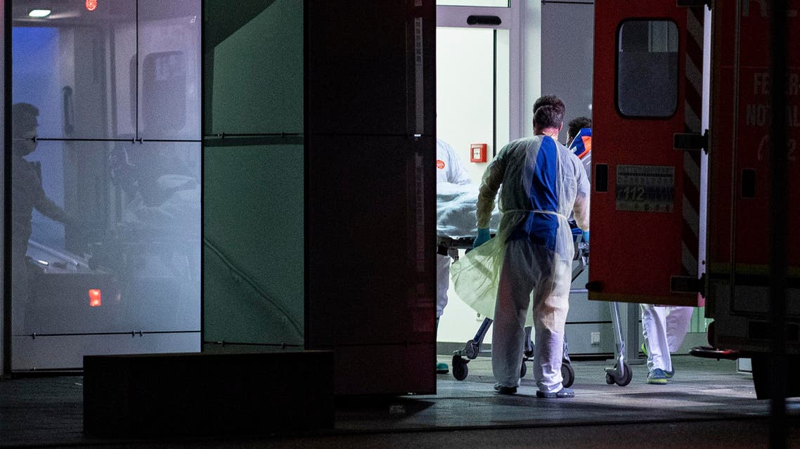 Medical staff in carry the first person infected with the coronavirus in the German state of North Rhine Westphalia out of an ambulance into the Liver and Infection Center of the University Hospital in Duesseldorf, Germany, Wednesday, Feb 26, 2020. (AP)