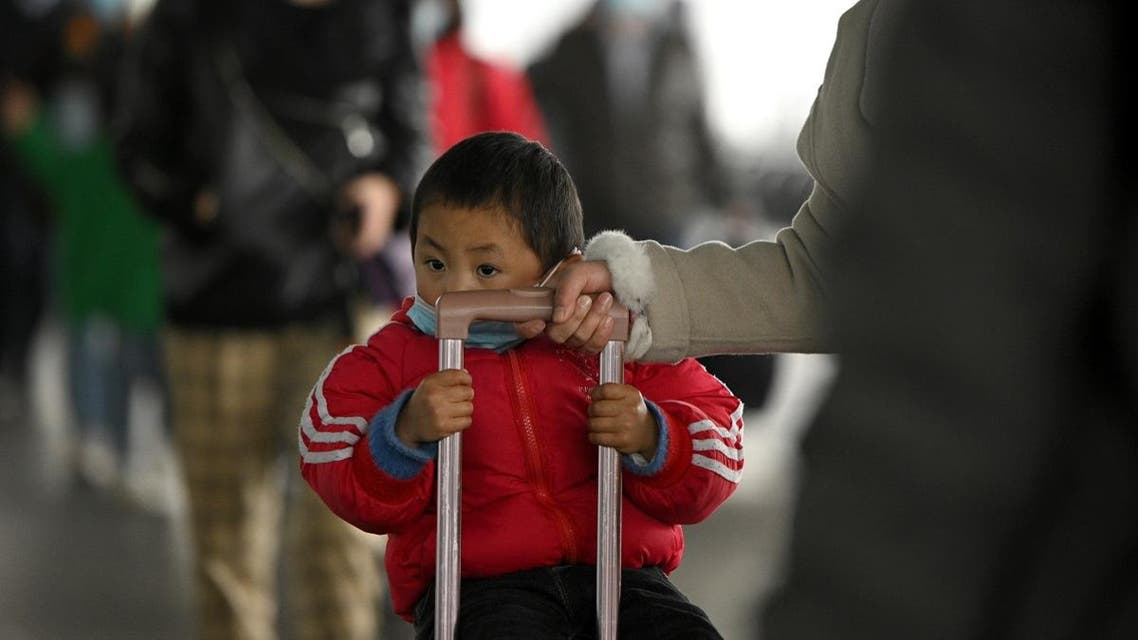 A child wearing a face mask arrives at Changsha railway station in Changsha, the capital of Hunan province on March 8, 2020. (AFP)