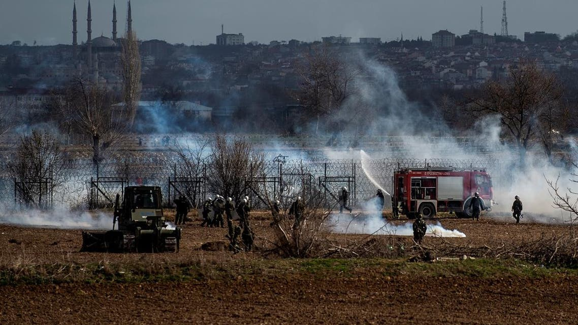 Greek soldiers and riot police officers stand stand amid clouds of tear gas at the Greece-Turkey border during clashes between migrants and riot police in the village of Kastanies on March 7, 2020. (AFP)
