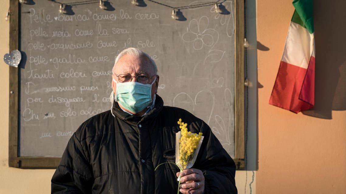 Life inside a red zone: A man wearing a protective mask holds a bouquet of flowers on a street outside on the 16th day of quarantine in San Fiorano, one of the 11 small towns in northern Italy that has been on lockdown since February. (Reuters)