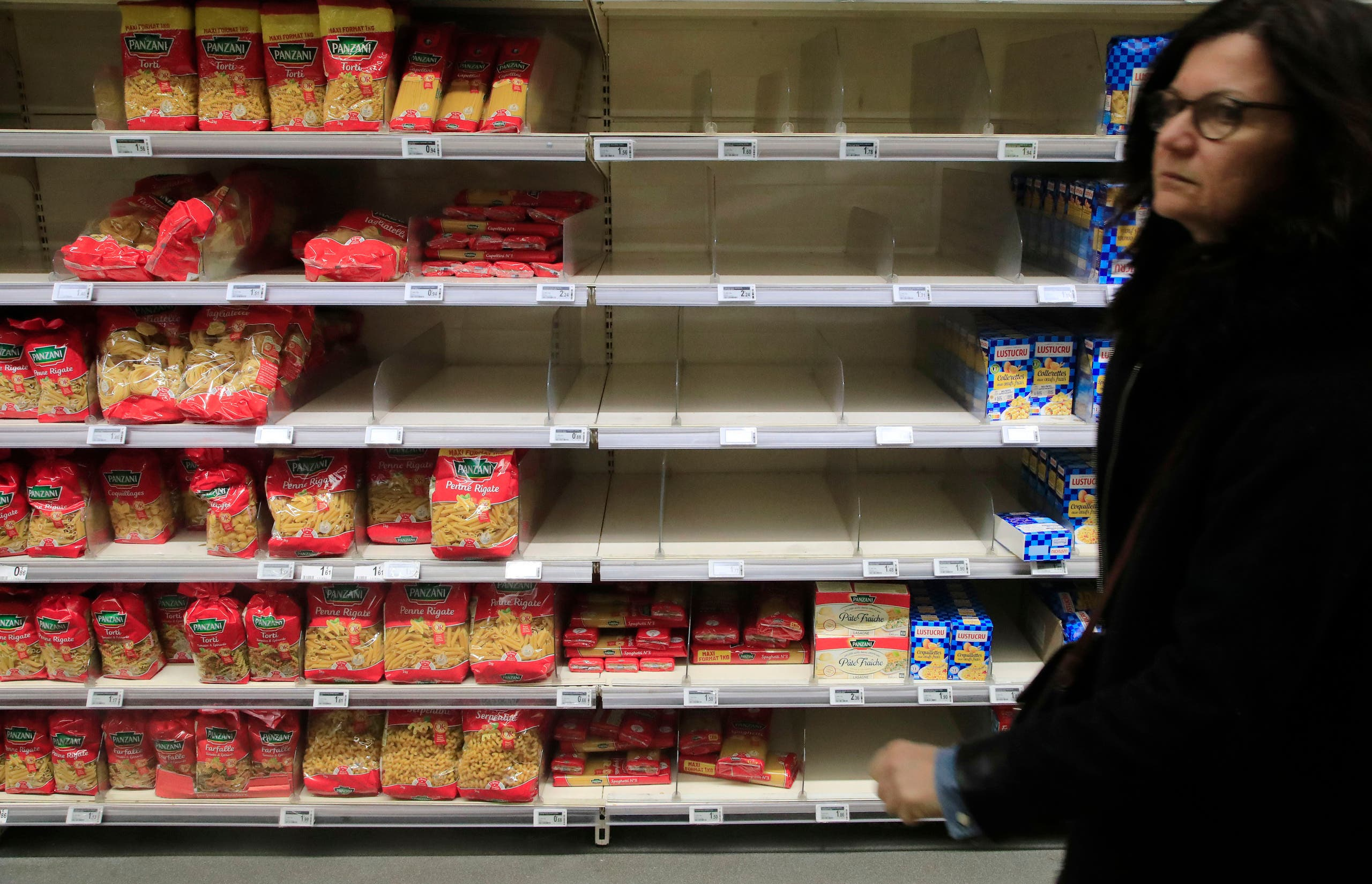 A woman walks past empty shelves at a supermarket in Paris, on March 9, 2020. Global share markets have plunged as panicked investors fled to the safety of bonds and the yen to hedge the economic trauma of the coronavirus. (AP)