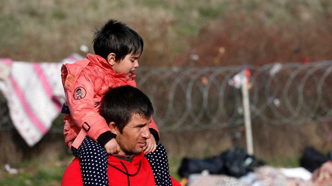 A man carries his son on his shoulder in a field where migrants camp out in Edirne, near the Turkish-Greek border on Sunday, March 8, 2020. (AP)