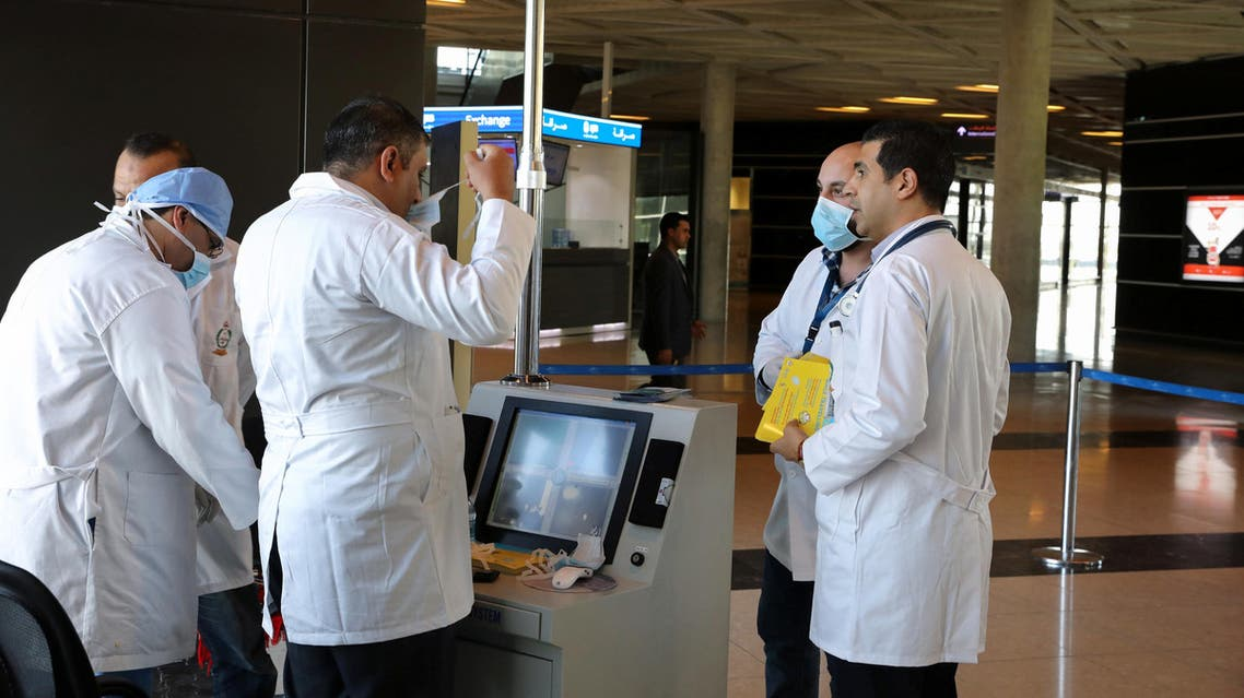Medical staff wear protective gear before checking passengers with thermal scanners for coronavirus symptoms, at Queen Alia International Airport in Amman, Jordan, March 4, 2020. (Reuters)