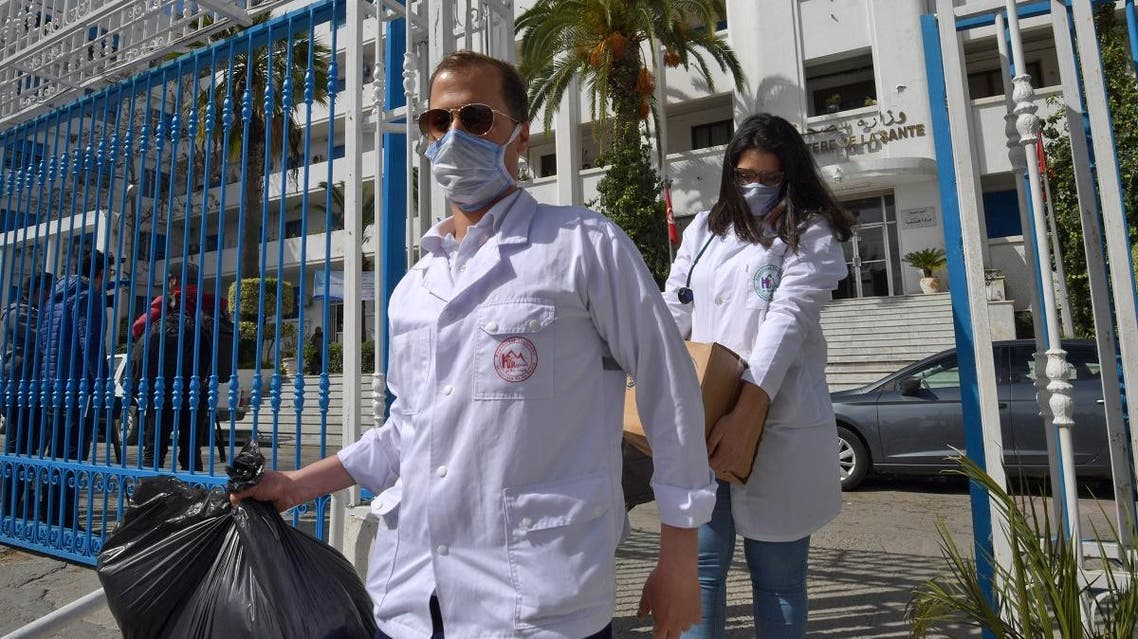 Emergency doctors and nurses who have been trained to handle the coronavirus disease cases, exit the Tunisian health ministry premises in the capital Tunis after collecting supplies on March 3, 2020. (AFP)