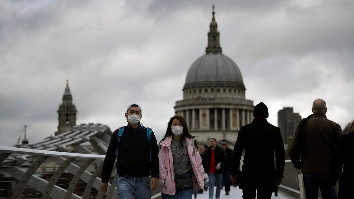 People wearing face masks walk across the Millennium footbridge backdropped by the dome of St Paul's Cathedral in London, Tuesday, March 10, 2020. (AP)