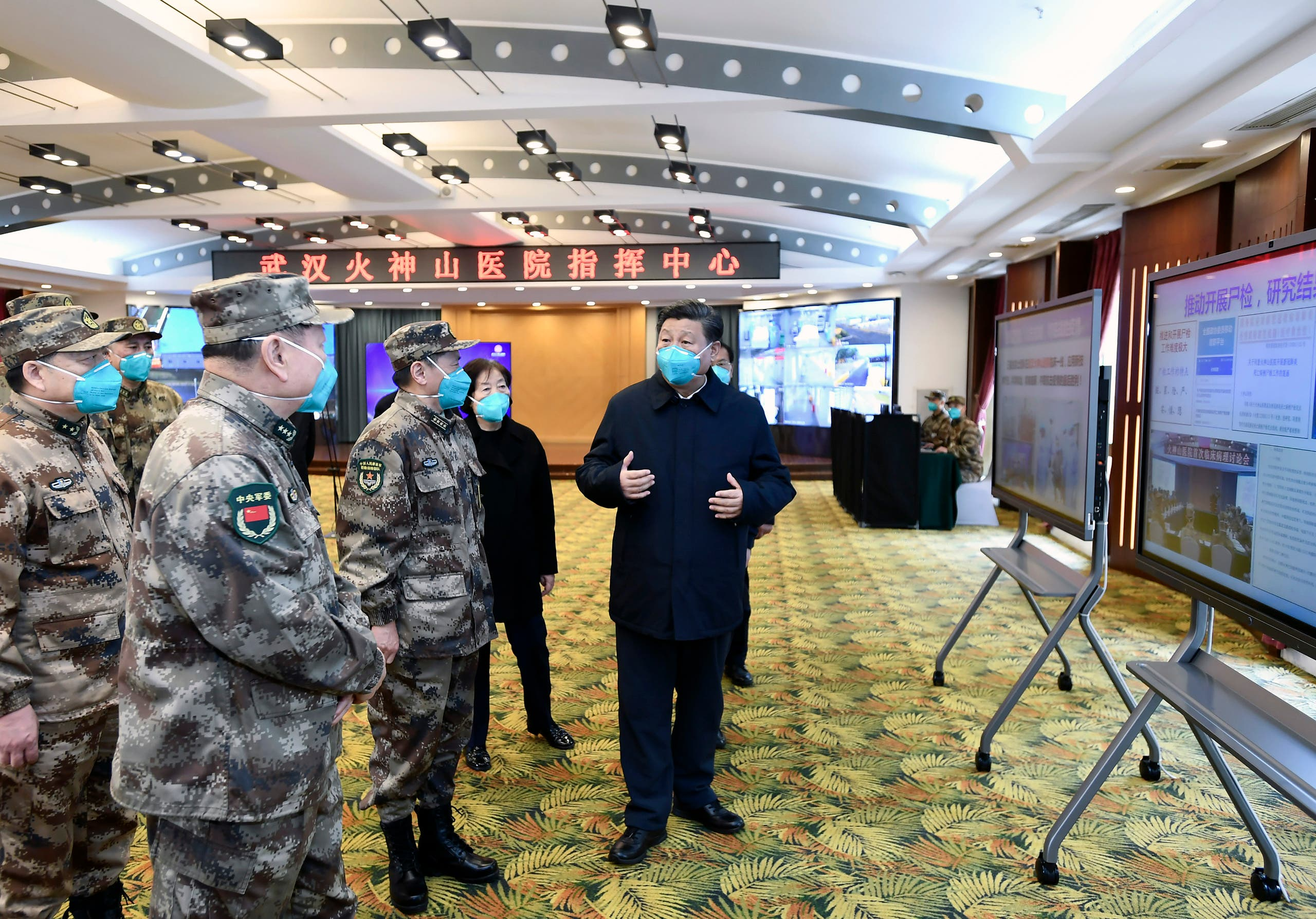 Chinese President Xi Jinping, right, is briefed about the Huoshenshan Hospital in Wuhan in central China's Hubei Province, on Tuesday, March 10, 2020. (AFP)