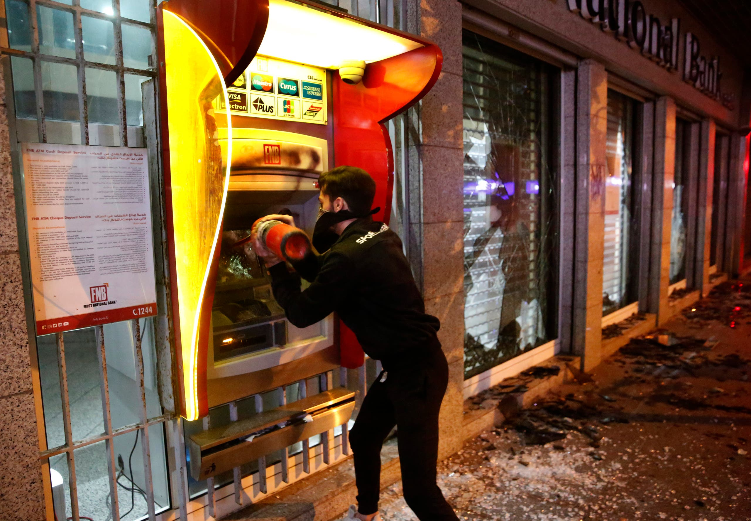 An anti-government protester destroys an ATM machine during ongoing protests against the Lebanese central bank's governor on Jan. 14, 2020 in Beirut. (AP)