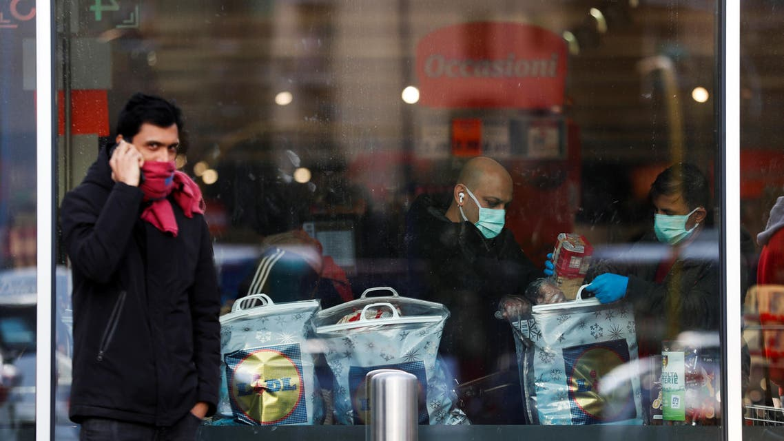 A person talks on the phone while people are shopping in a supermarket to stock up on food and goods, after a decree orders for the whole of Italy to be on lockdown in an unprecedented clampdown aimed at beating the coronavirus, in Rome, Italy, March 10, 2020. (Reuters)