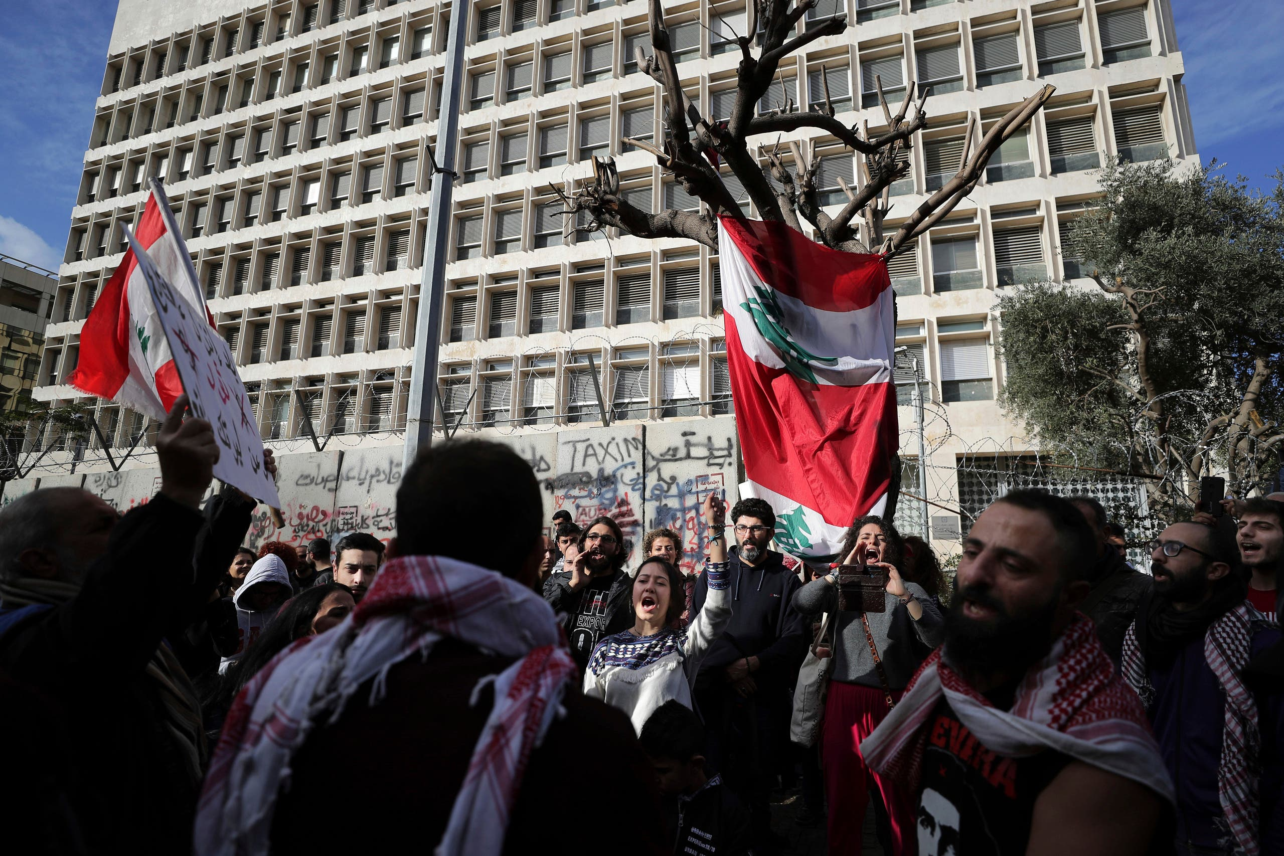 Anti-government protesters chant slogans, during ongoing protests against the Lebanese government in front of the Central Bank in Beirut on Feb. 1, 2020. (AP)